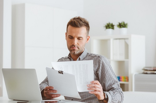 man sitting at computer looking at papers